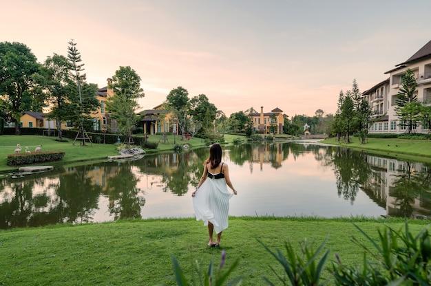 Tył azjatyckiej kobiety w sukience stojącej na trawie w pobliżu jeziora z europejskim tłem zamku