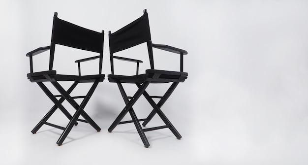 Tył czarnego krzesła reżysera dwóch wykorzystania w produkcji wideo lub przemyśle filmowym i kinowym na białym tle.