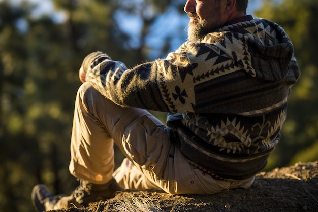 Tył człowieka relaksujący i podziwiający malowniczy las ze skalistego wzgórza. turysta podziwiający widok na las ze szczytu wzgórza. turysta robiący sobie przerwę i relaksujący się na szczycie wzgórza