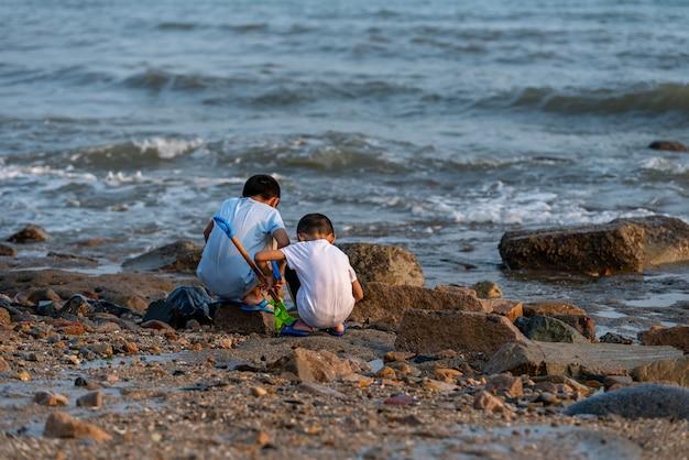 Tył dwójki dzieci bawiących się w górę rzeki.