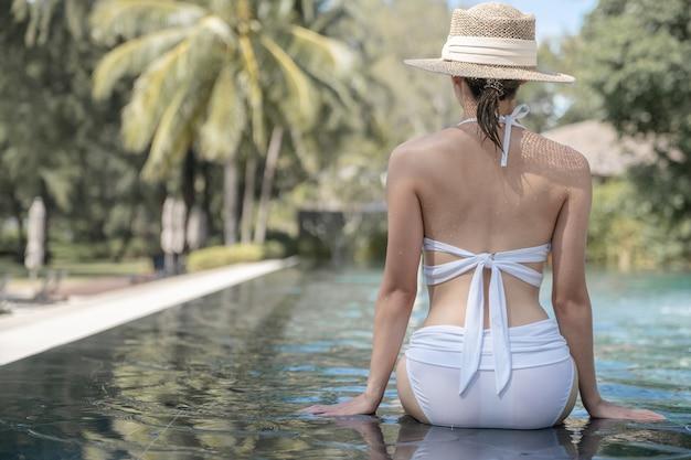 Tył kobiety sobie bikini i słomkowy kapelusz relaks w basenie. koncepcja zabiegów spa.