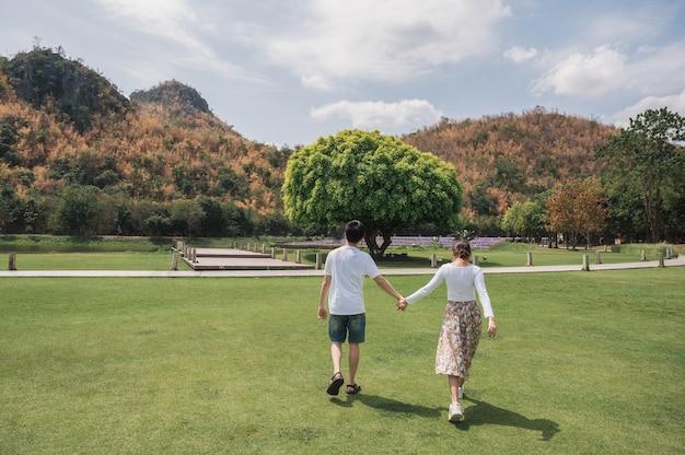 Tył młoda para azjatyckich spaceru trzymając się za ręce na trawie i duży wzrost drzewa w parku