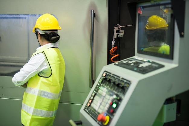 Tył pasa w górę azjatycka pracownica fabryki sprawdza pick and place electronic machinery dla linii montażowej do montażu powierzchniowego płytek drukowanych. przemysł mikroprocesorowy.