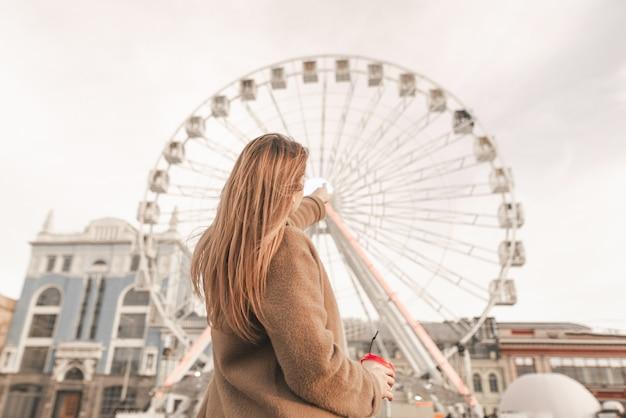 Tył stylowej dziewczyny stoi na ulicy z filiżanką kawy w dłoniach, ubrana w wiosenny strój codzienny, pokazuje palec na diabelskim młynie