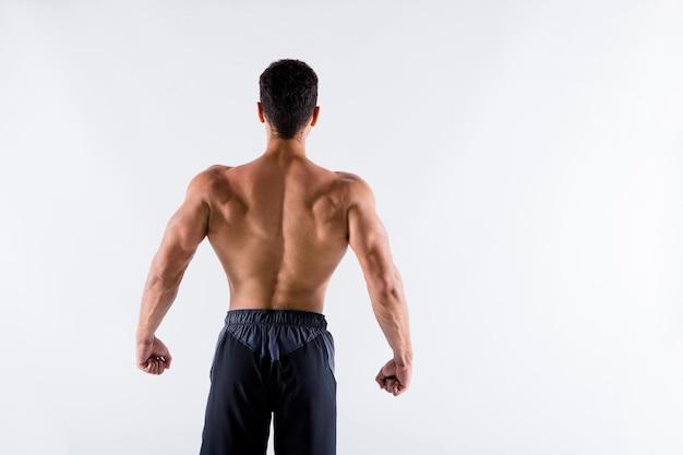 Tył z tyłu widok sportowego opalonego faceta kultury fizycznej białka steroidowego pokazującego mięśnie