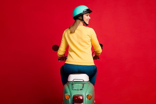 Tył z tyłu za widokiem dziewczyny jazdy motorowerem z boku na czerwonej ścianie