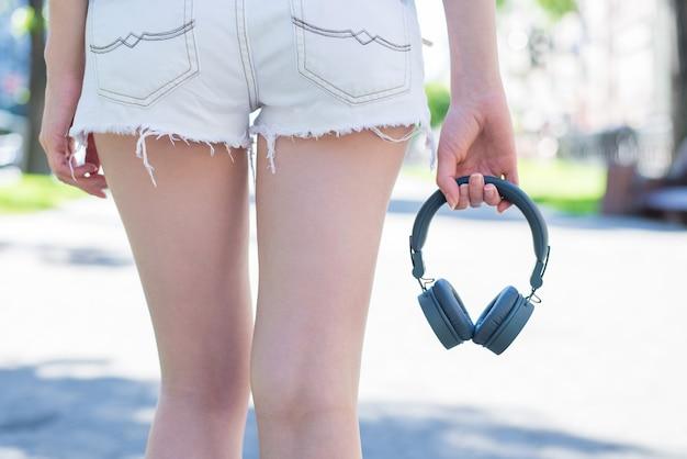 Tył z tyłu za zbliżeniem przycięty widok dopasowanego kształtu smukłe, atrakcyjne biodra kobiety ubrane w mini szorty trzymające przenośny portative szary bez drucianych słuchawek