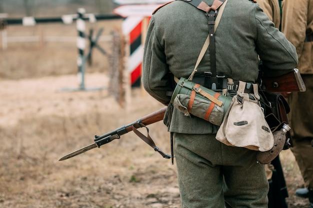 Tył żołnierza wehrmachtu w mundurze i karabinie
