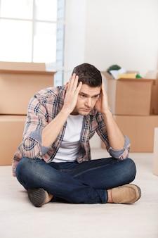 Tyle pudeł do rozpakowania. przygnębiony młody mężczyzna siedzi na podłodze i trzyma głowę w dłoniach, podczas gdy kartony leżą w tle