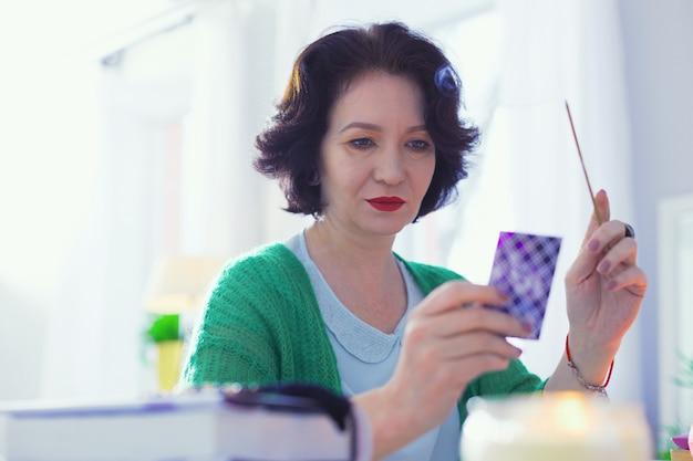 Tyle znaczeń. sprytny wróżbita czytający kartę tarota, trzymając w ręku pałeczkę aromatu