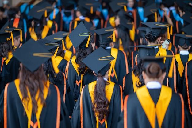 Tyłki absolwentów idą, aby wziąć udział w ceremonii rozdania dyplomów na uniwersytecie