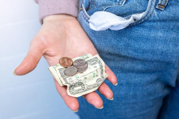Tylko jeden dolar i drobna gotówka, pusta kieszeń. brak pieniędzy. kryzys gospodarczy, ubóstwo, pojęcie bezrobocia. konsekwencje izolacji osób z koronawirusem podczas kwarantanny. stopy inflacji. wzrost cen.