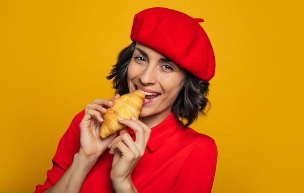 Tylko jeden kęs! młoda francuzka, ubrana w paryski styl, z czerwonym beretem, trzymająca w dłoniach francuską bułkę i nie mogąca się powstrzymać przed ugryzieniem.