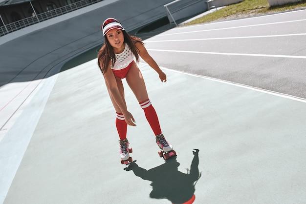 Tylko piękna kobieta z przodu jeździ na rolkach w skateparku, wyglądając na skupioną