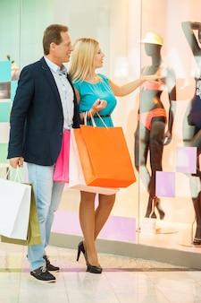 Tylko spójrz na to! pełna długość wesołej dojrzałej pary robi zakupy w centrum handlowym, podczas gdy kobieta wskazuje manekin