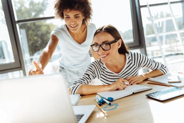 Tylko spójrz. wesoły uśmiechnięte młode kobiety korzystające z laptopa i siedzące przy stole, przygotowując się do zajęć