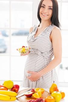 Tylko świeże i zdrowe jedzenie dla mojego dziecka. przycięty obraz kobiety w ciąży trzymającej talerz z sałatką owocową