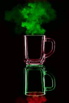 Tylko szklanka na czarnej ścianie z odbiciem. czerwone i zielone, z parą. odosobniony.