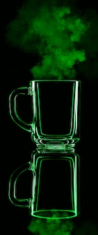 Tylko szklanka na czarnej ścianie z odbiciem. kolor zielony, z parą. odosobniony.
