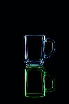 Tylko szklanka na czarnej ścianie z odbiciem. kolory zielony i niebieski. odosobniony.