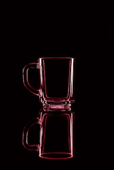 Tylko szklanka na czarnym tle z odbiciem. czerwone kolory. odosobniony.