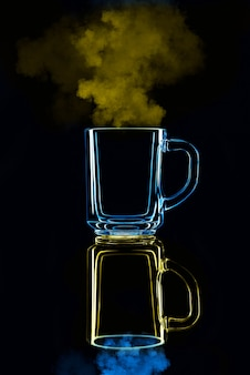 Tylko szklanka na czarnym tle z odbiciem. niebiesko-żółty, z parą. odosobniony.