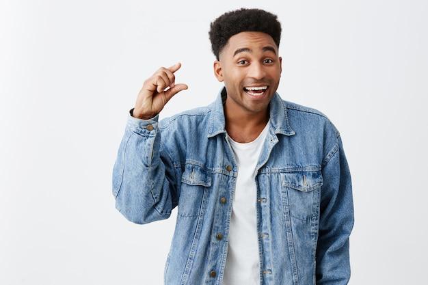 Tylko trochę. bliska odosobniony portret młodego przystojnego mężczyzny o czarnej skórze z fryzurą afro w białej koszulce pod niebieską jeansową kurtką gestykuluje ręką, patrząc w kamerę z radością