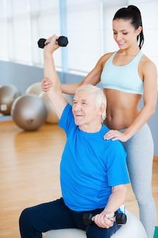 Tylko trochę wyżej! pewna siebie fizjoterapeutka pracująca ze starszym mężczyzną w klubie fitness