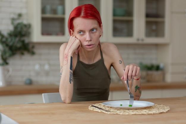 Tylko trzy groszki. chuda rudowłosa kobieta z bulimią jedząca tylko trzy zielone groszki