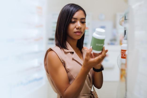 Tylko uwaga. ładna międzynarodowa dziewczyna stojąca w pół pozycji i wybierająca tabletki do pielęgnacji skóry