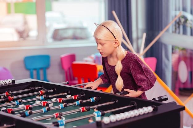 Tylko uwaga. piękne długowłose dziecko pochyla głowę i gra w sztuczną piłkę nożną