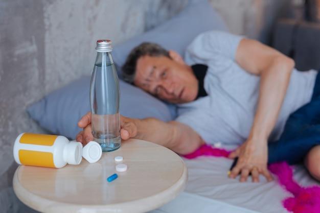 Tylko woda. selektywne skupienie się na szklanej butelce wypełnionej wodą i dojrzałym mężczyzną leżącym na łóżku