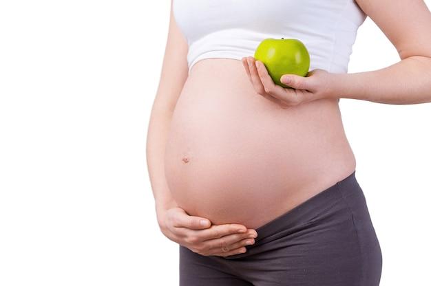 Tylko zdrowa żywność. przycięty obraz kobiety w ciąży trzymającej zielone jabłko stojąc na białym tle