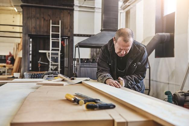 Tylko zrównoważone drewno i narzędzia ręczne portret mężczyzny rasy kaukaskiej wygładzającego deskę do drewna