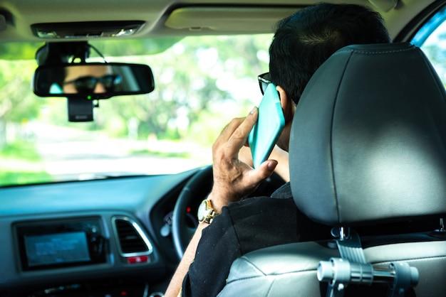 Tylna część człowieka korzysta z inteligentnego telefonu komórkowego w samochodzie