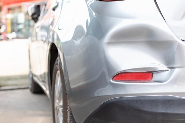 Tylna część nowego srebrnego samochodu zostaje uszkodzona przez przypadek