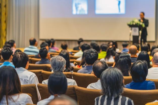 Tylna część publiczności słuchającej mówcy na scenie