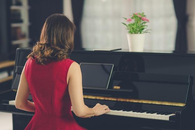 Tylna część siedzącej kobiety uczącej się i uczącej nowych umiejętności gry na pianinie podczas lekcji online z tabletu. proces w stylu filmowym i vintage.