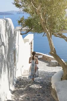 Tylna część turysty kobieta chodzenie po schodach w miejscowości oia, santorini z morzem śródziemnym. santorini europa letni cel.