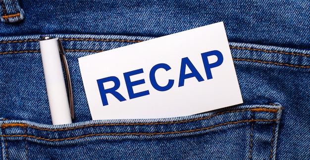 Tylna kieszeń niebieskich dżinsów zawiera biały długopis i białą kartę z napisem recap