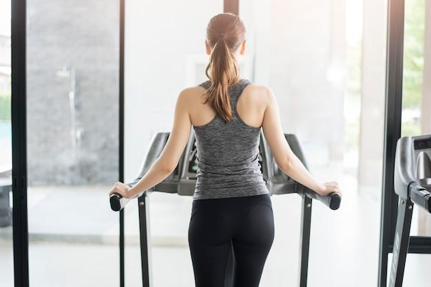 Tylna sport kobieta jogging na karuzeli w gym, zdrowy styl życia