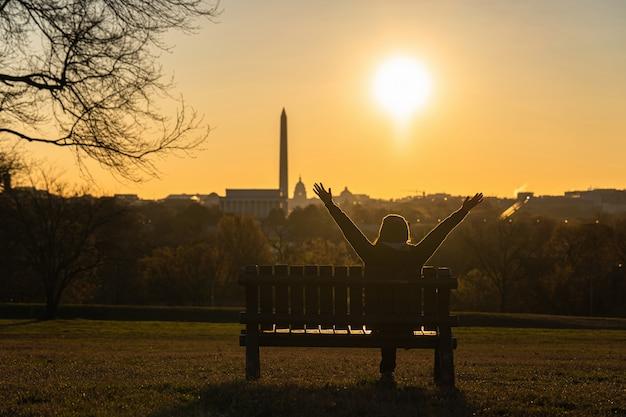Tylna strona azjatyckiej kobiety siedzącej i podnoszącej ręce do sukcesu nad punktem orientacyjnym w waszyngtonie, który widzi kapitol stanów zjednoczonych, pomnik waszyngtonu i pomnik lincolna w czasie wschodu słońca,
