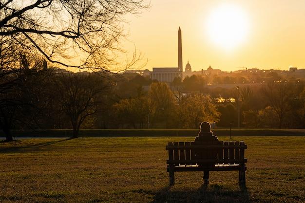 Tylna strona azjatyckiej kobiety siedzącej samotnie nad punktem orientacyjnym w waszyngtonie, w którym widać kapitol stanów zjednoczonych