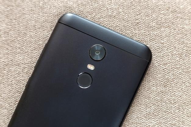 Tylna strona odizolowywająca z telefonu komórkowego kciuka odcisku palca skanerowania urządzeniem, kamery i błysku oświetleniem na lekkim płótno kopii przestrzeni tle czarny telefon komórkowy. nowoczesna technologia i koncepcja projektowania smartfonów.