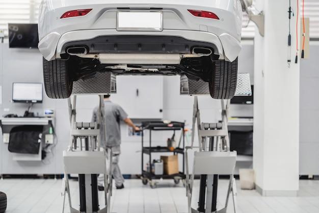 Tylna strona samochodu podniesiona w serwisie samochodowym i mechanika azjatyckiego sprawdzanie i palnik opon w centrum serwisowym, które jest częścią salonu