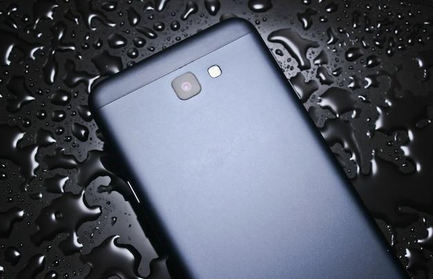 Tylna strona smartfona z kroplami wody na czarnym stole