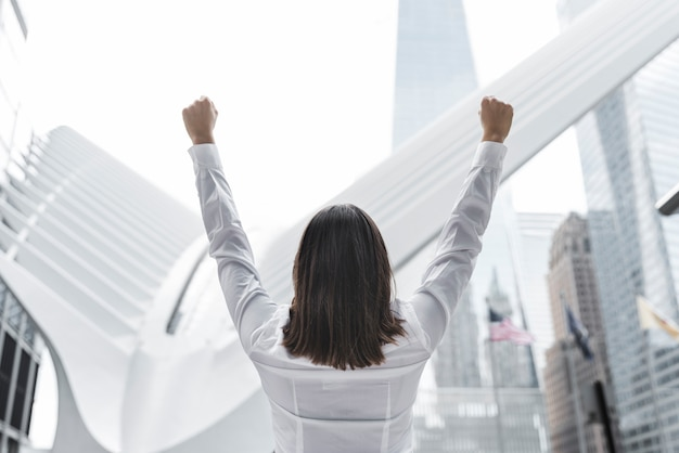 Tylna widok brunetki kobieta wyraża zwycięstwo