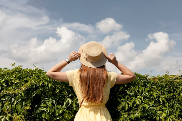 Tylna widok dziewczyna pozuje z rośliną