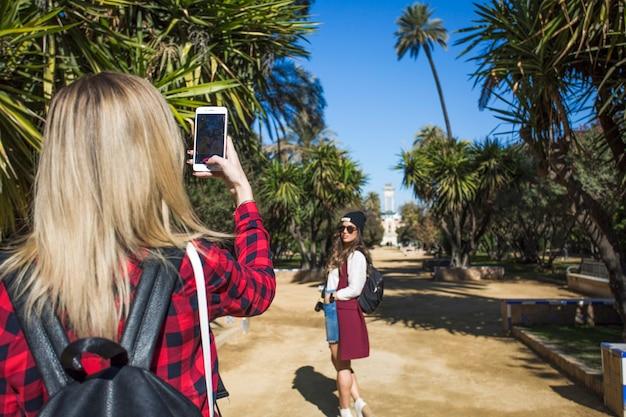Tylna widok kobieta bierze fotografię przyjaciel