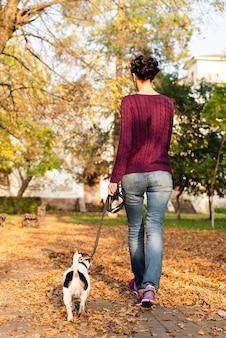 Tylna widok kobieta chodzi jej psa w parku